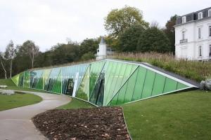 vista lateral derecho de muro cortina con forma de triángulos y cristales verdes en aiete