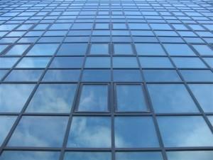 vista frontal de la cara lisa del muro cortina de aluminio en negro y vidrios azules