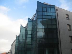muro cortina de aluminio con olas en la parte superior y vidrios azules