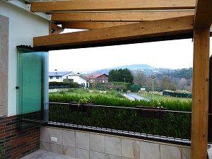 cortina de cristal abierta desde el interior en porche de madera