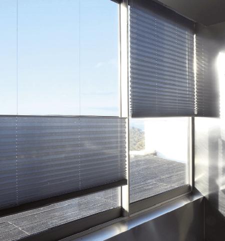 2 cortinas plisadas en gris sobre ventana