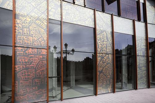 vidrios en ventanas de aluminio color burdeos y vidrio oscuro con vinilos en dorado