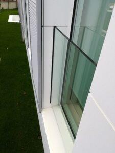 barandilla de vidrio empotrada en fachada blanca